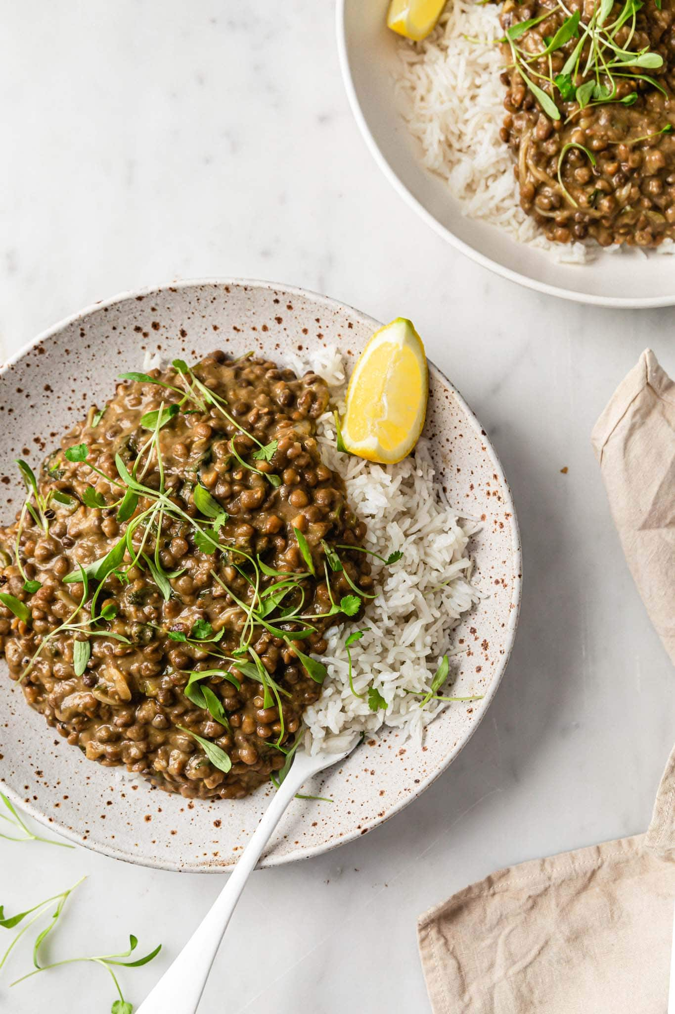 Whole Masoor Dal with basmati rice and silverware garnished with cilantro and served with a lemon wedge