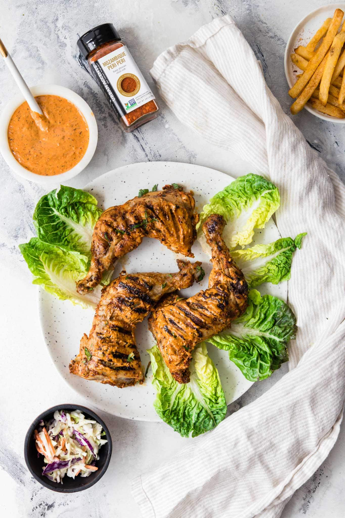 Tender Homemade Peri Peri Chicken on a round speckled plate with lettuce and a bowl of peri peri sauce on the side.