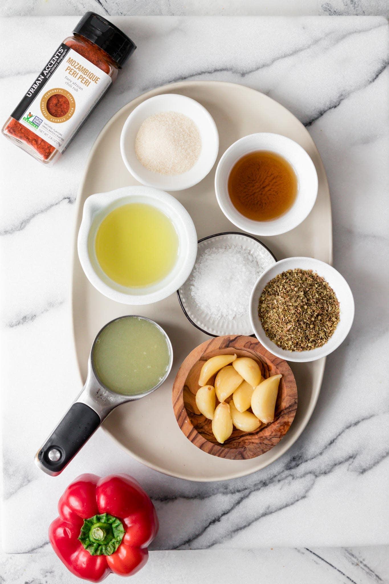 Ingredients for Peri Peri Sauce including peri peri seasoning, sugar, apple cider vinegar, oil, salt, oregano, lemon juice, garlic and red pepper.