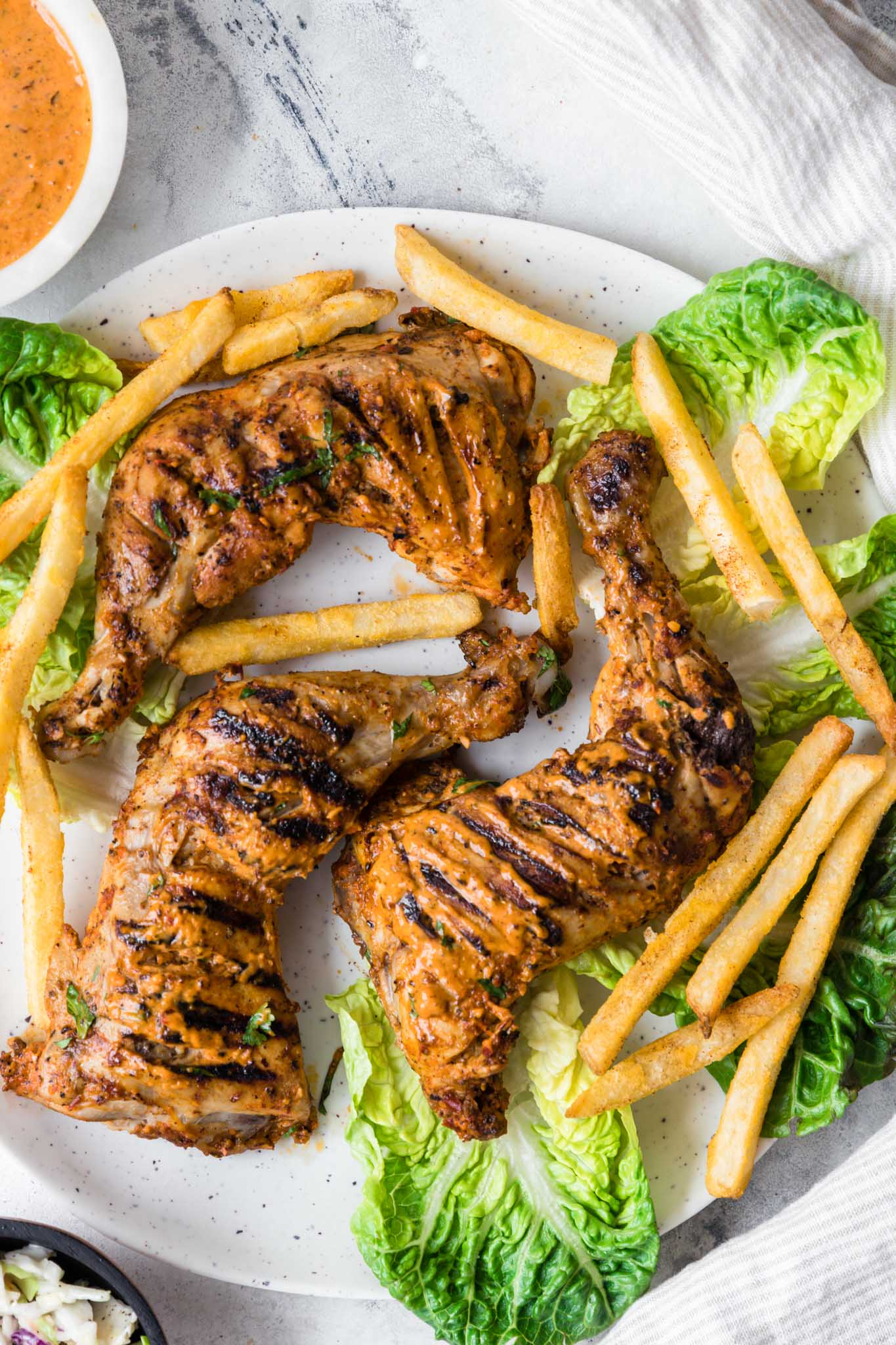 Tender Homemade Peri Peri Chicken on a round speckled plate with lettuce and french fries.