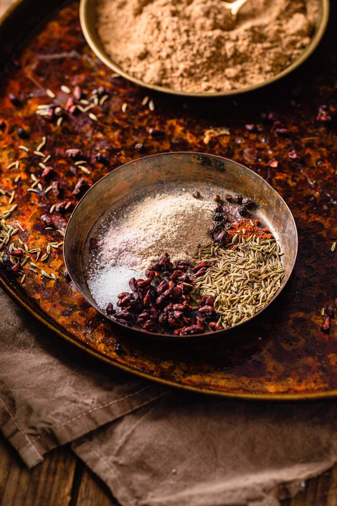 A brass bowl containing dried mango powder (amchur), dried pomegranate seeds (anardana), cumin seeds, black peppercorns, red chili powder, and sugar