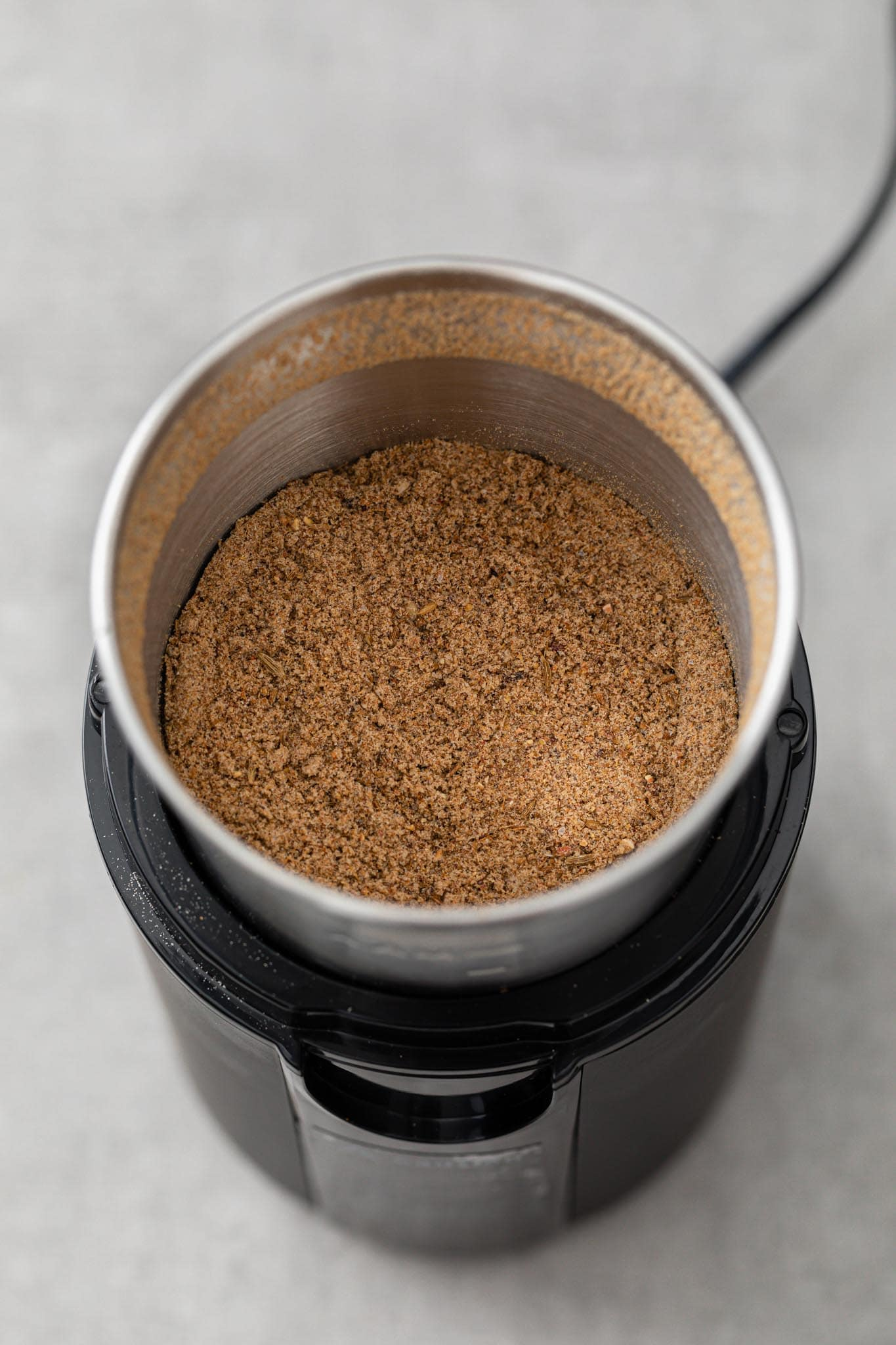 Ground chaat masala in a spice grinder ready to be stored