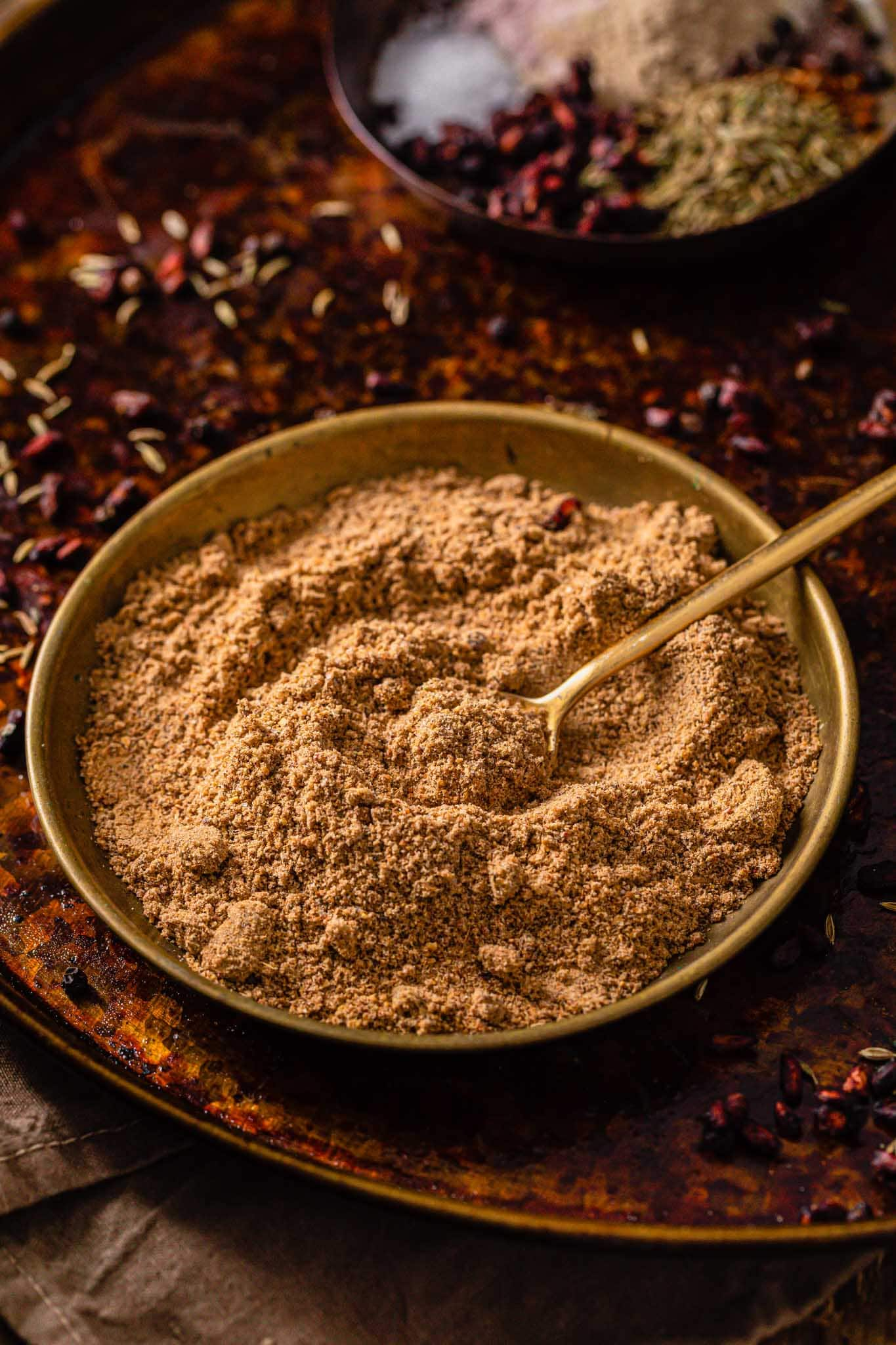 Chaat Masala powder in a gold bowl with a golden spoon sitting on a rustic surface