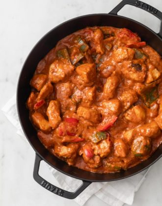 Saucy Chicken Shashlik with bell peppers and onions in a black skillet with a white napkin underneath