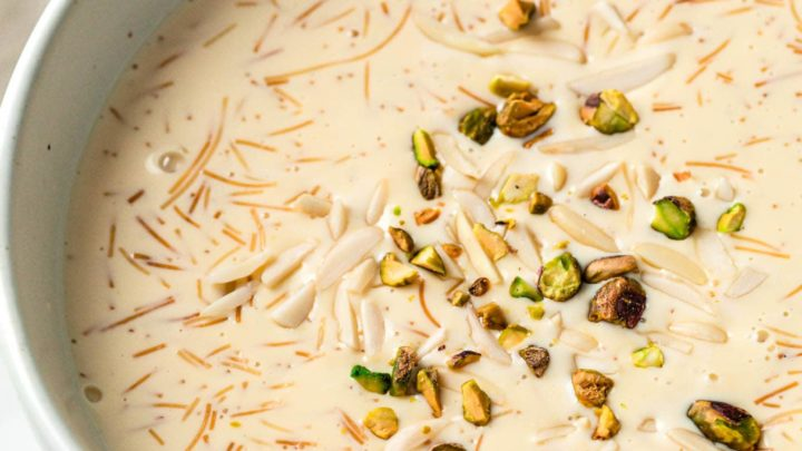 A large bowl with sheer khurma served with spoons and nuts in small bowls