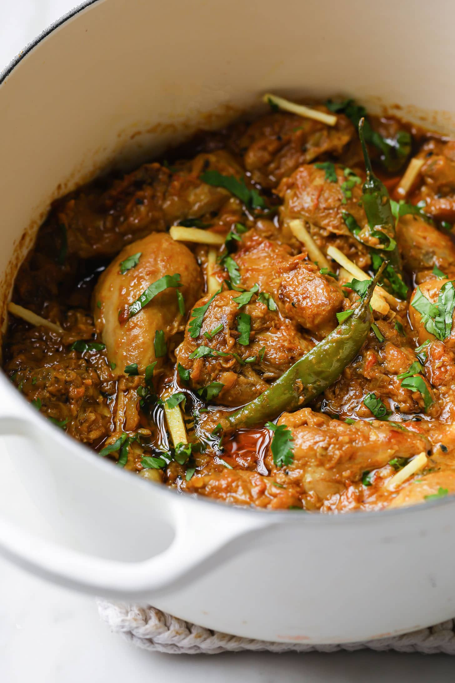 Achari Chicken garnished with cilantro and julienned ginger in a white Dutch oven