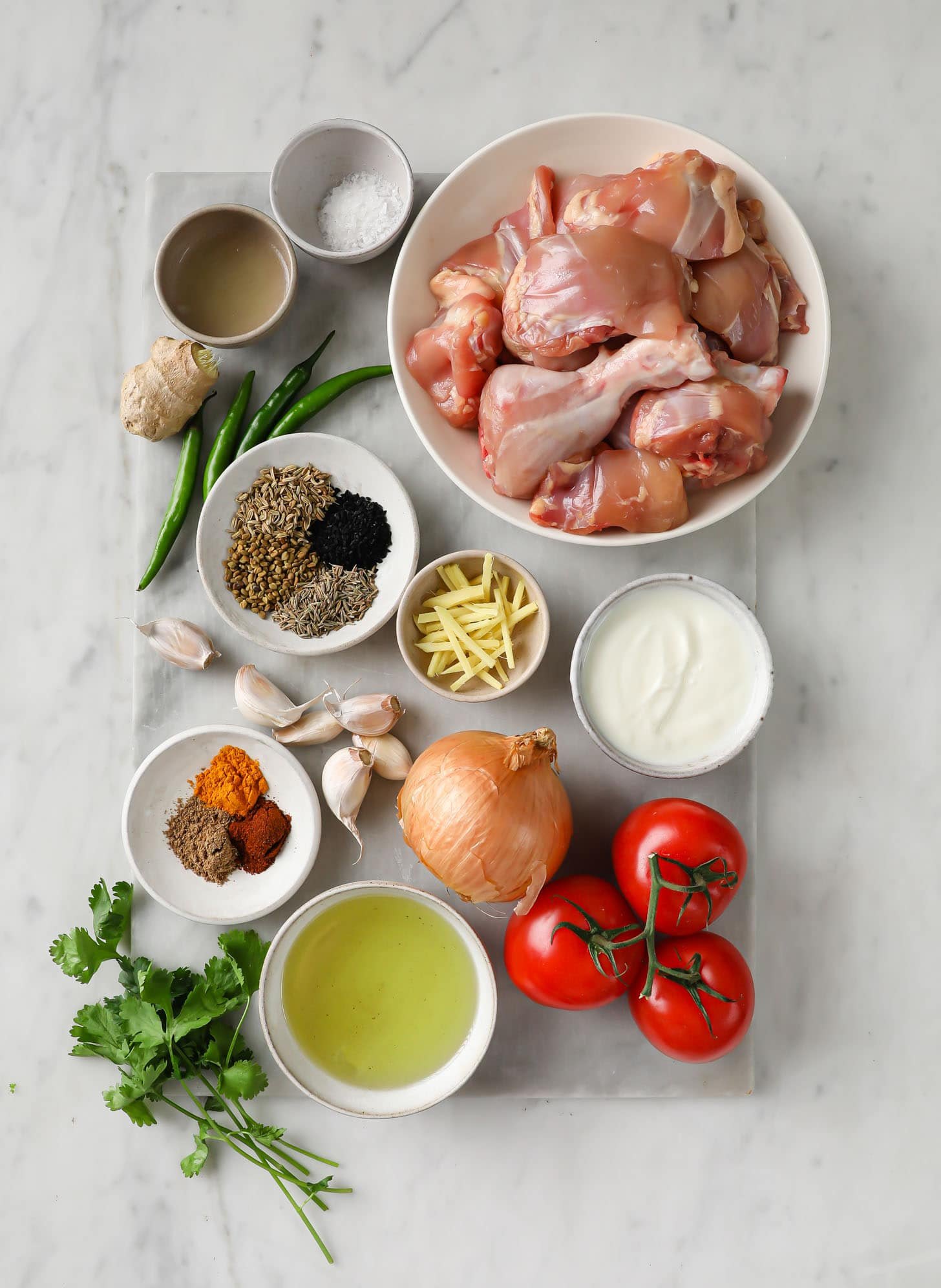 Ingredients for Achari Chicken including yogurt, tomatoes, onions, whole spices, ground spices, garlic and ginger placed on a marbled surface