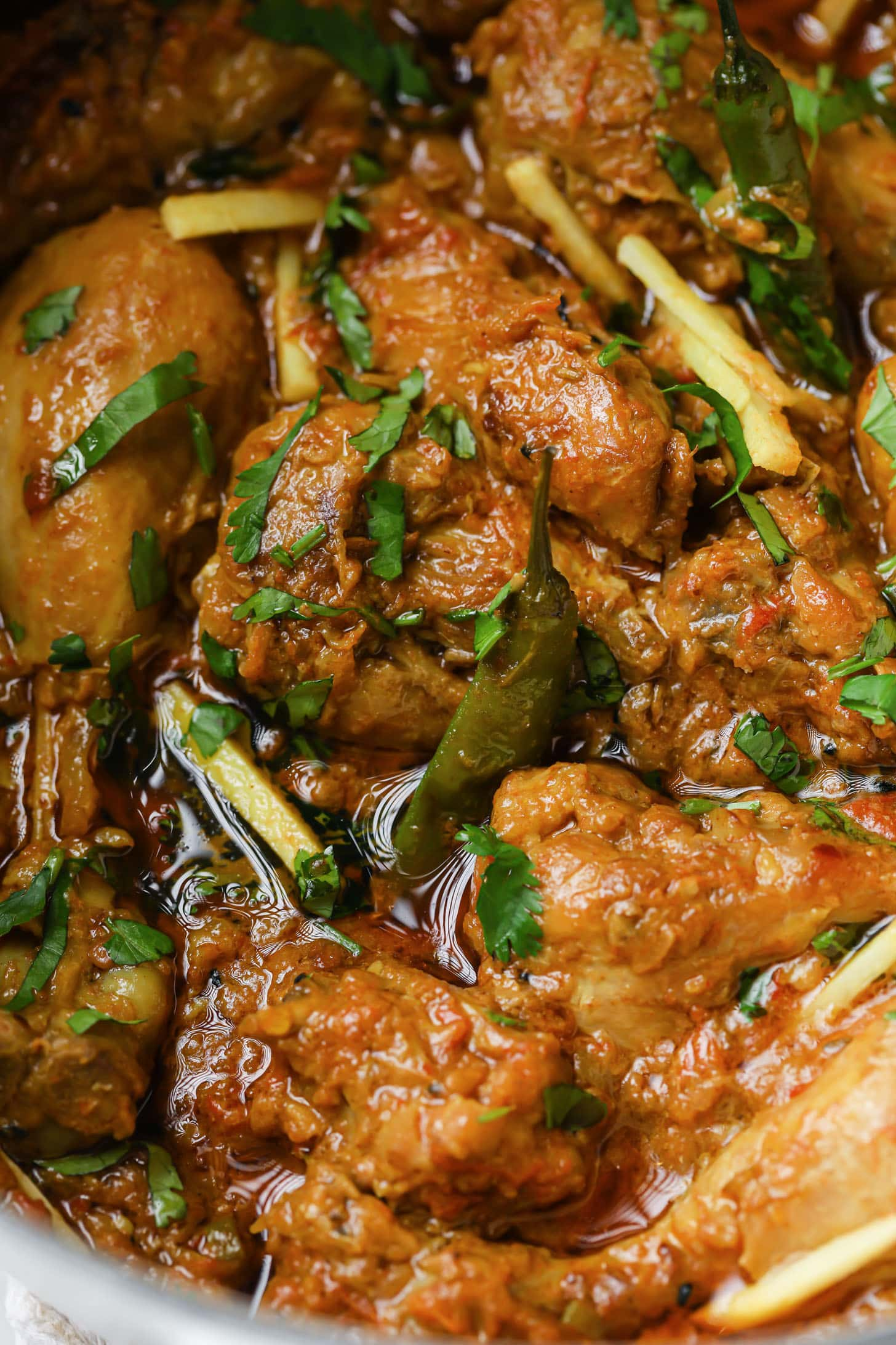 A close up of Achari Chicken garnished with cilantro and julienned ginger