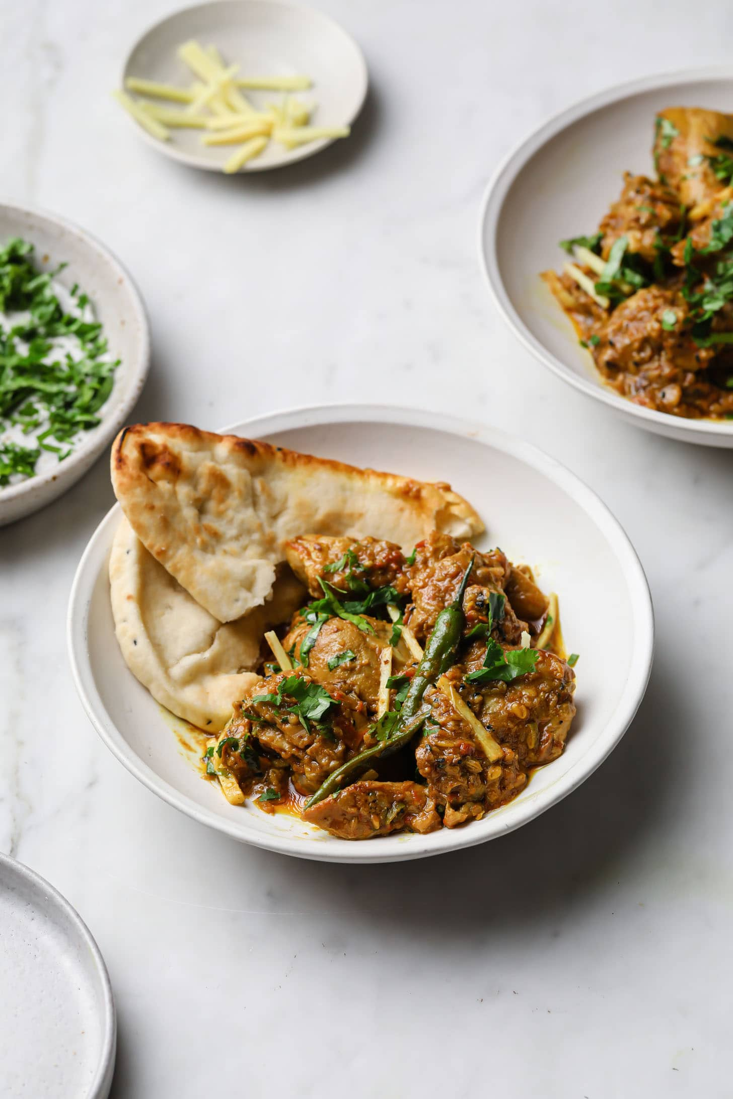 A white bowl with Achari Chicken and naan