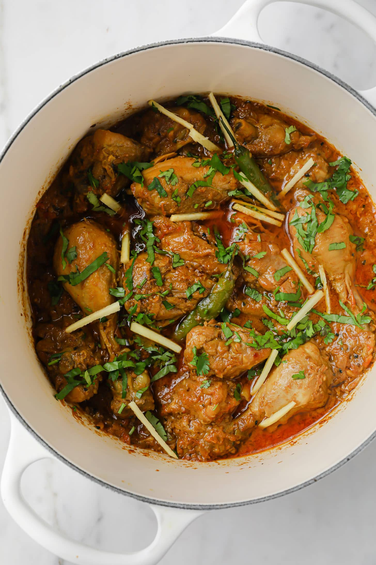 A finished shot of Achari Chicken Curry garnished with cilantro and julienned ginger