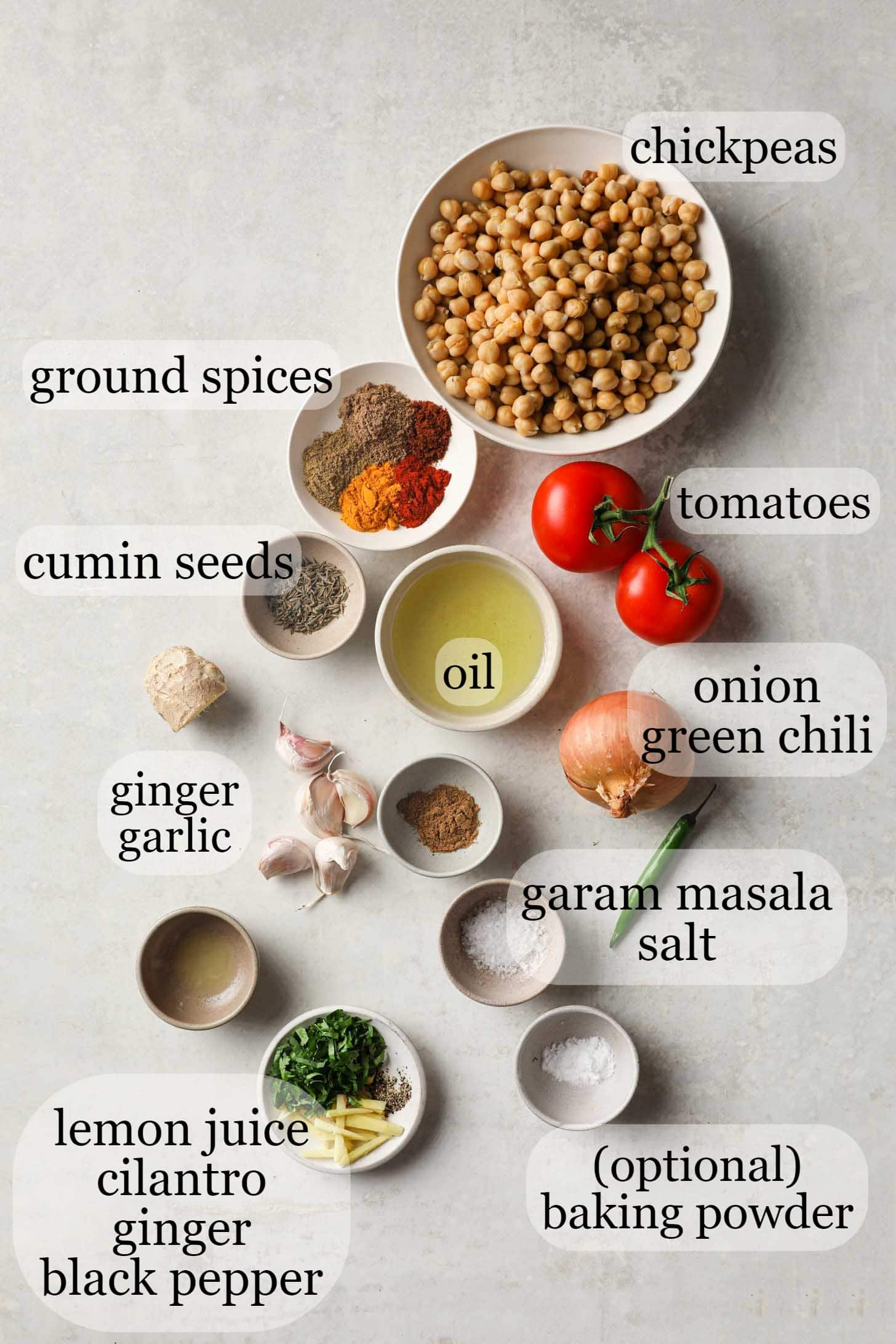 Chickpeas, tomatoes, spices, oil, onions, garlic, ginger, among other Chana Masala ingredients on a gray surface