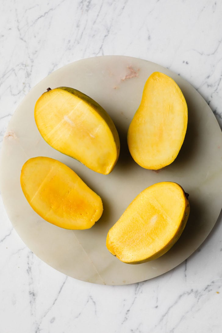 Cut open mangoes on a round tray on a marbled surface