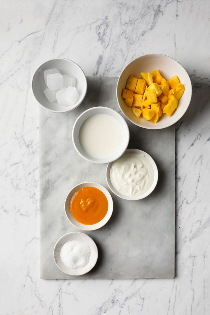 Frozen mangoes, milk, yogurt, mango pulp, ice, and sugar placed on a marbled surface