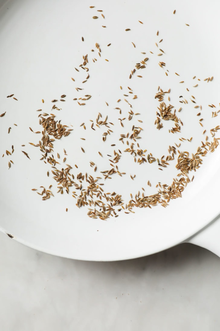 Toasting cumin seeds in a white skillet