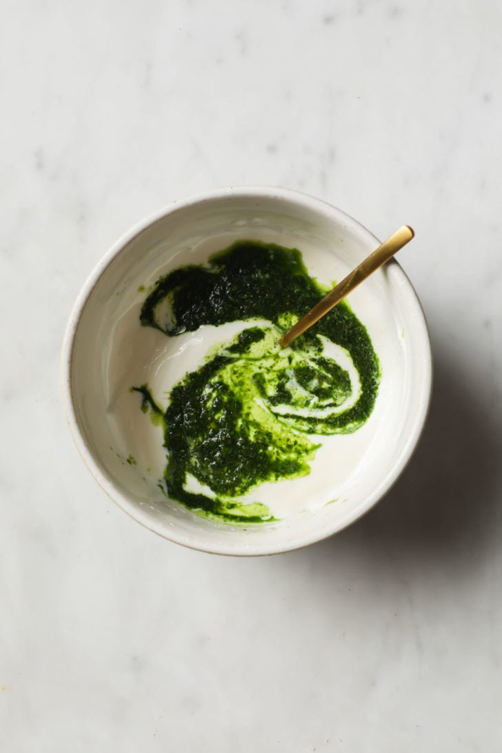 A bowl with green chutney being mixed with yogurt