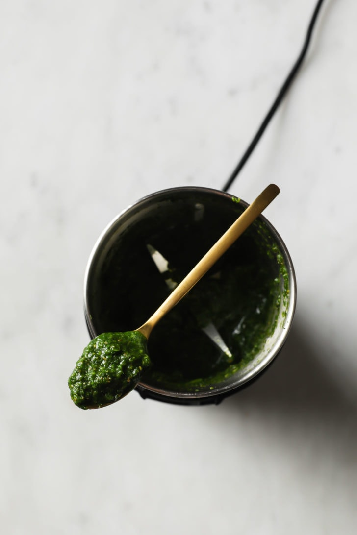 A wooden spoon on top of a spice grinder showing round green chutney