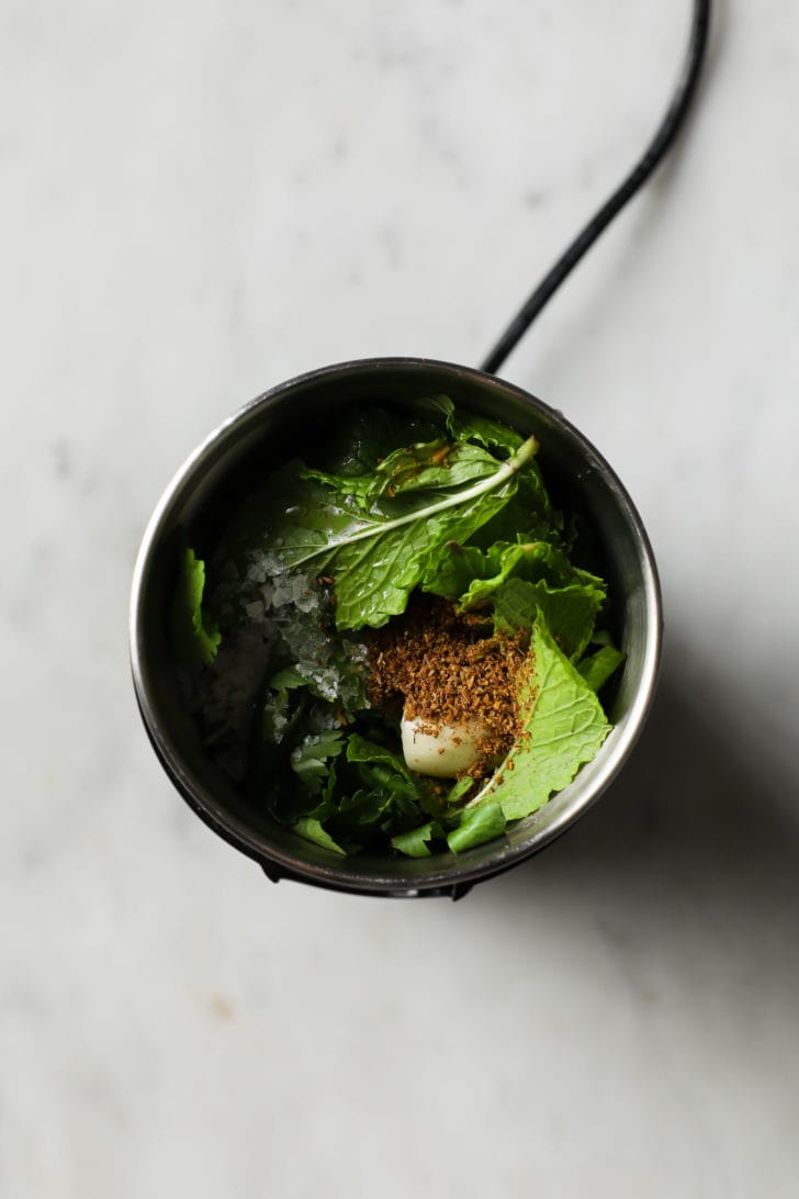 Cilantro, mint, salt, garlic, and ground cumin in a spice grinder