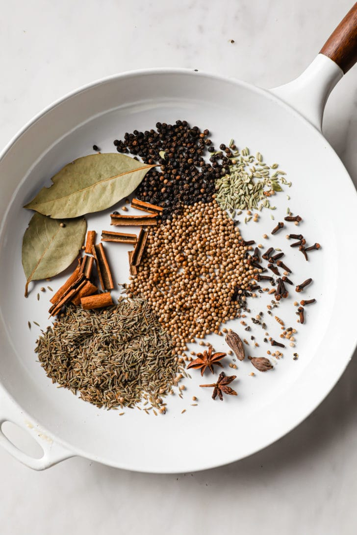 Whole Spices in a white skillet ready to be toasted for garam masala