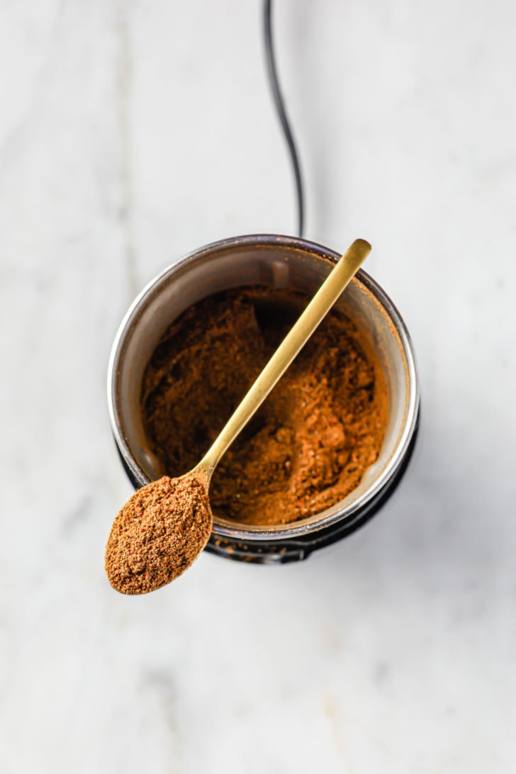 A spoon with freshly ground spices resting on top of a spice grinder