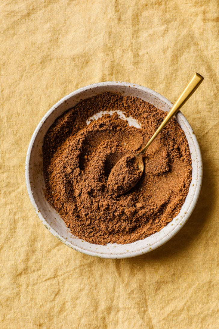 Garam Masala in a speckled bowl with a gold spoon on a yellow background