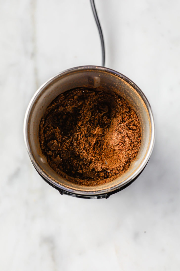 A spice jar with ground, toasted spices
