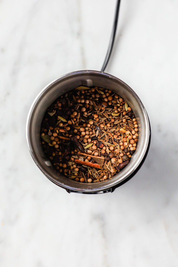 Toasted spices in a spice grinder ready to be ground for garam masala